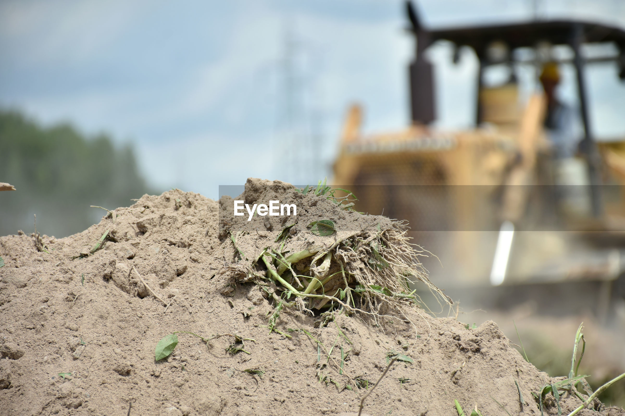 A pile of soil isolated with blurred image of tractor working in a field