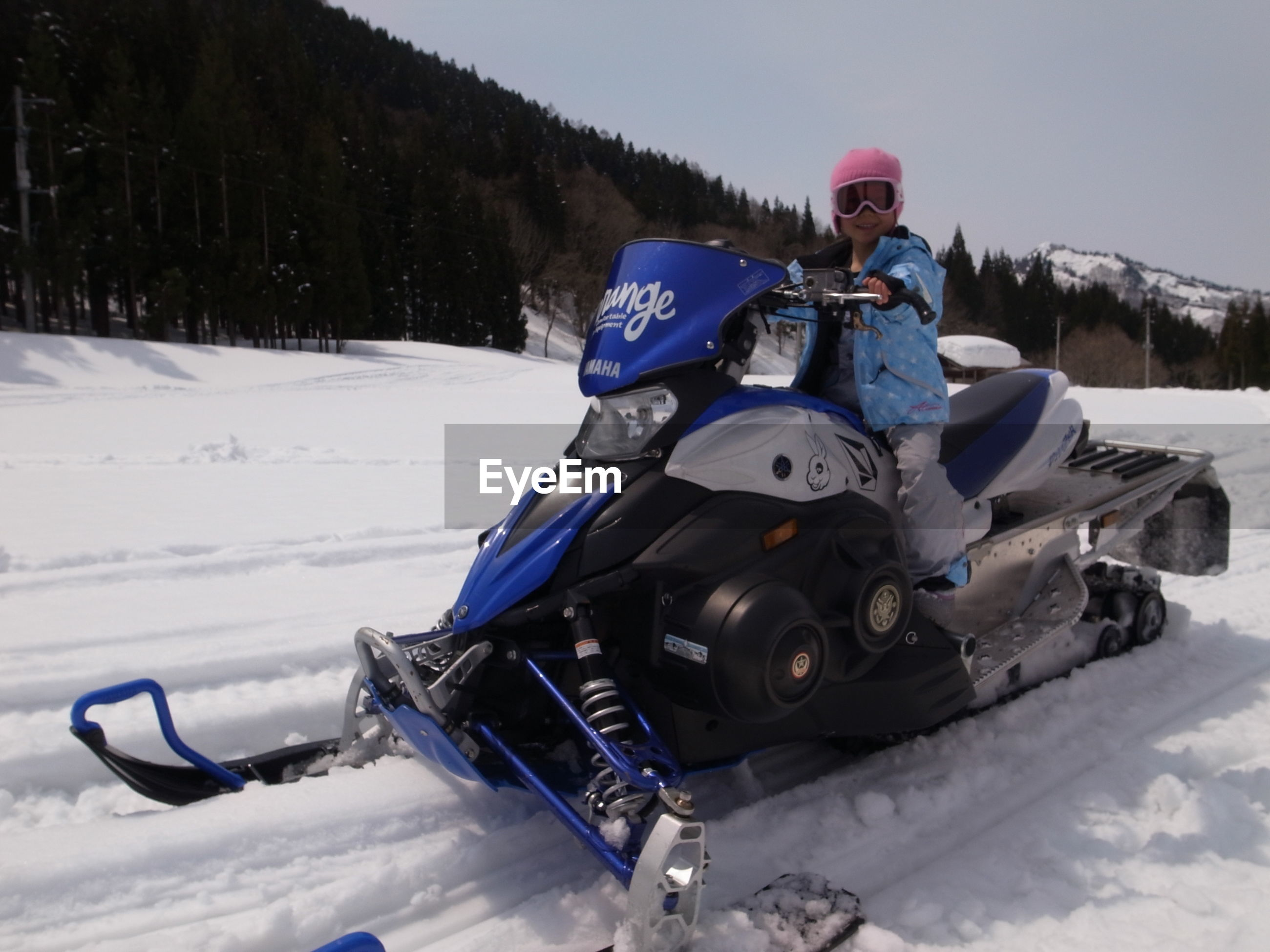Low angle view of girl riding motorcycle on snow