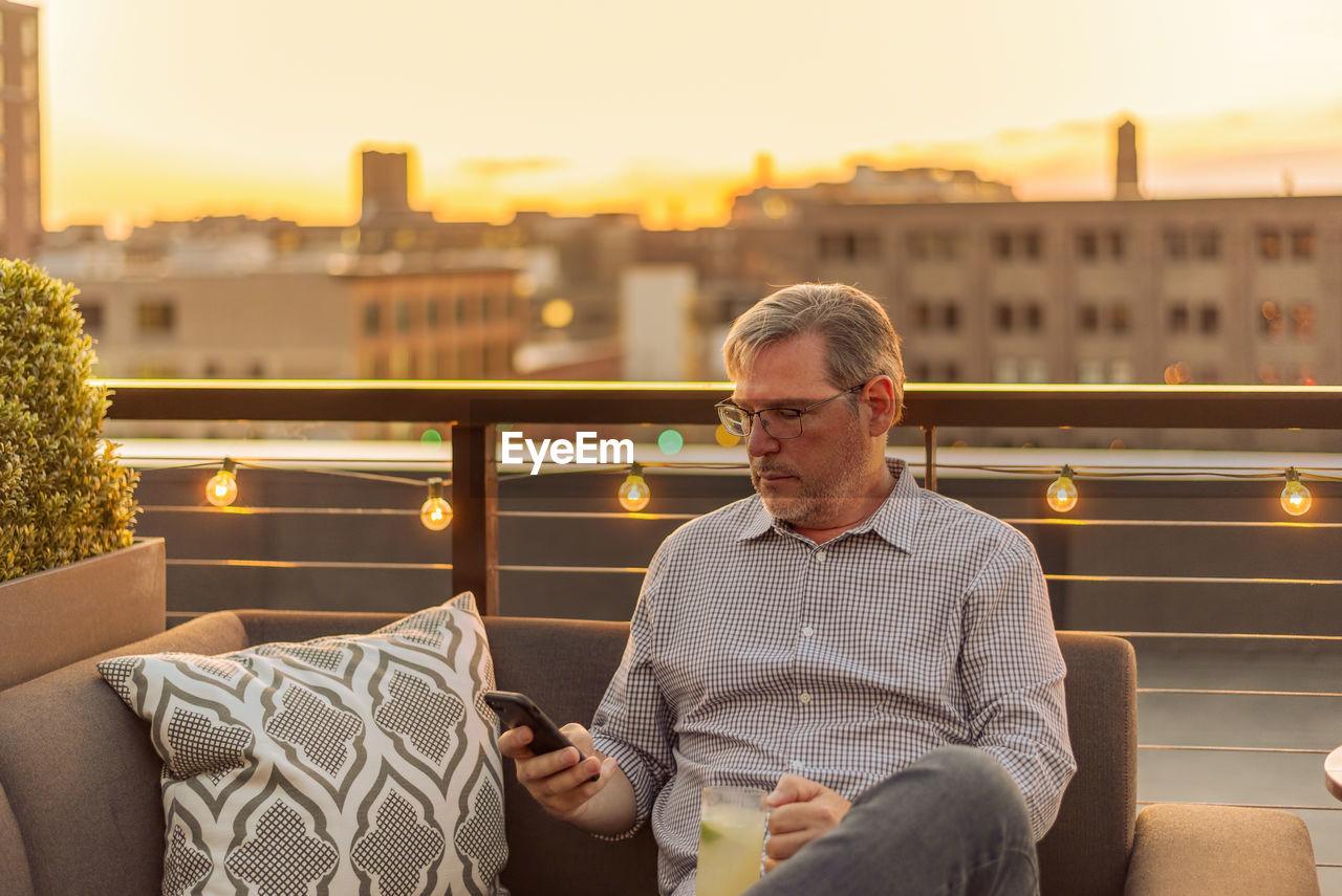 Mature man using phone at terrace during sunset