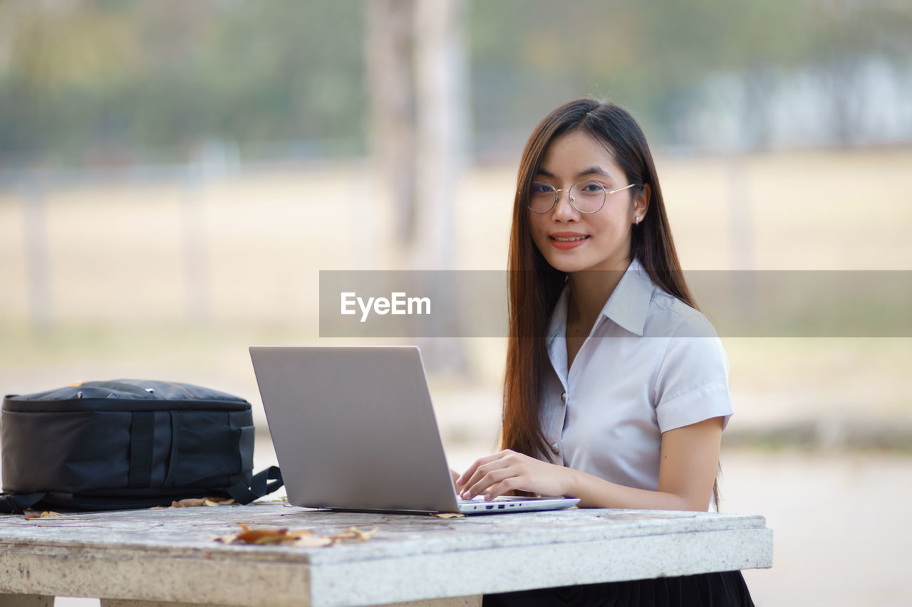 computer, laptop, using laptop, one person, wireless technology, technology, table, young adult, young women, women, adult, portrait, focus on foreground, connection, real people, glasses, smiling, beautiful woman, hairstyle, surfing the net
