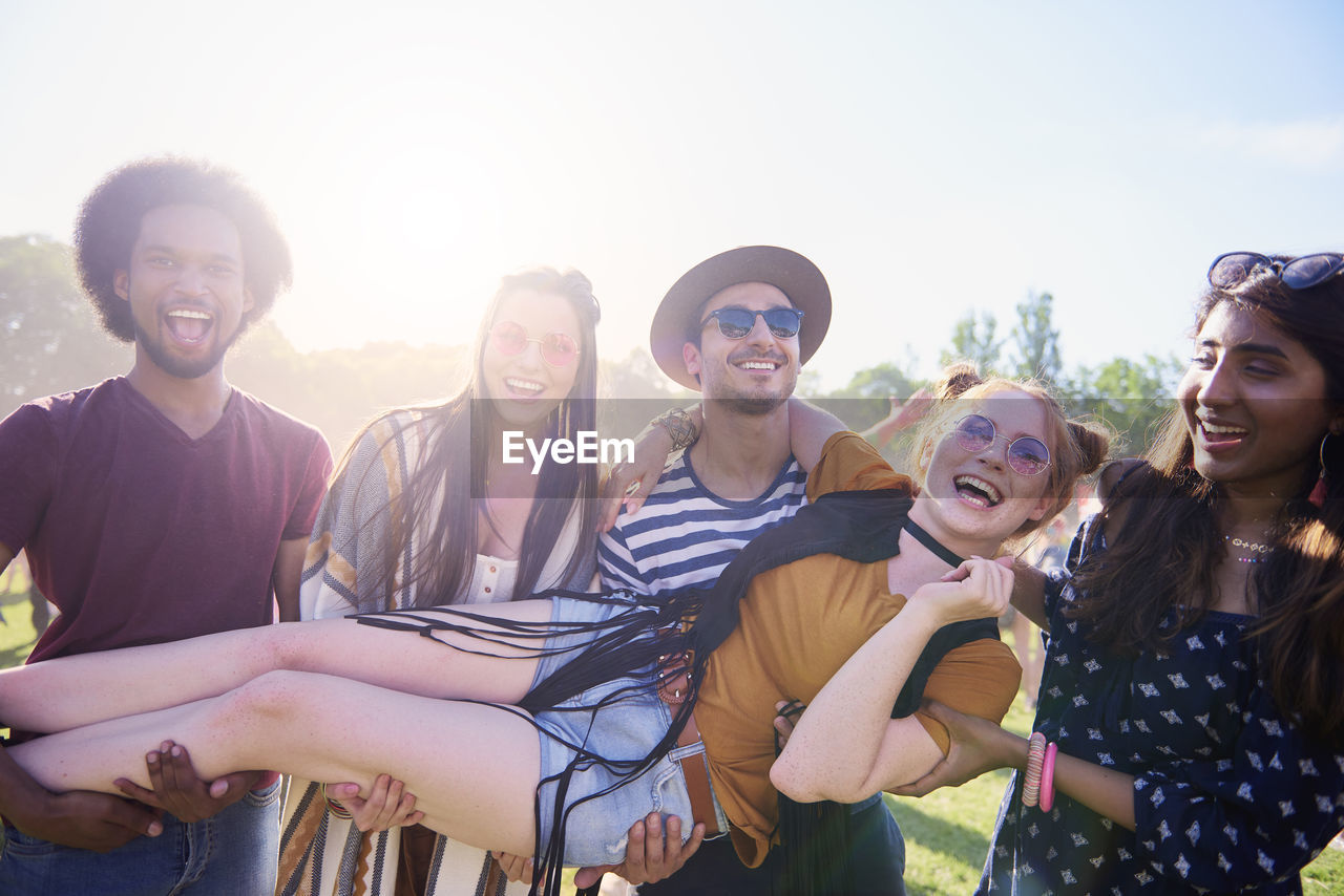 happiness, smiling, young adult, emotion, leisure activity, friendship, group of people, young women, enjoyment, fun, togetherness, young men, lifestyles, real people, cheerful, portrait, waist up, people, casual clothing, outdoors, positive emotion
