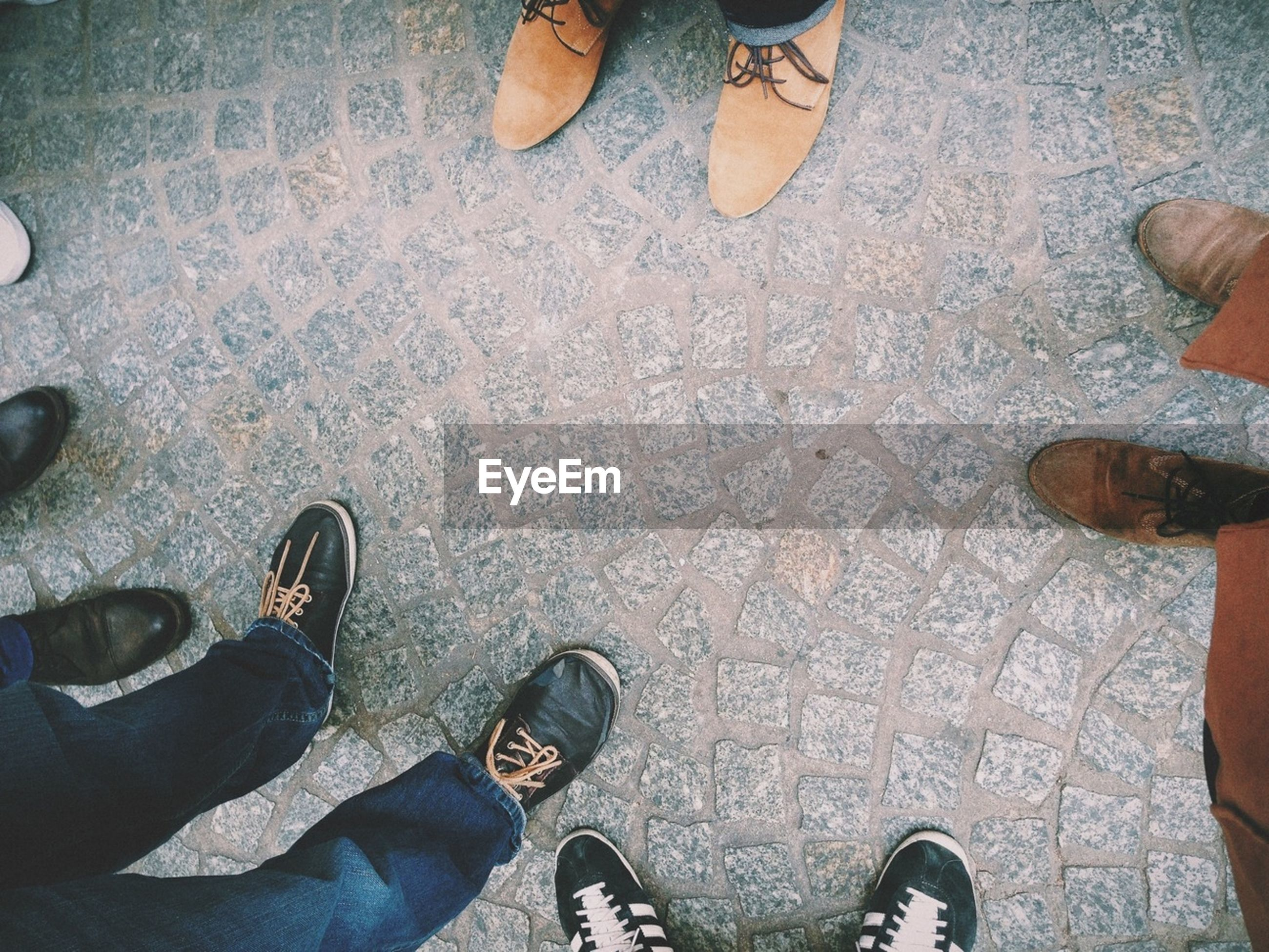 View of people legs standing on cobble stone