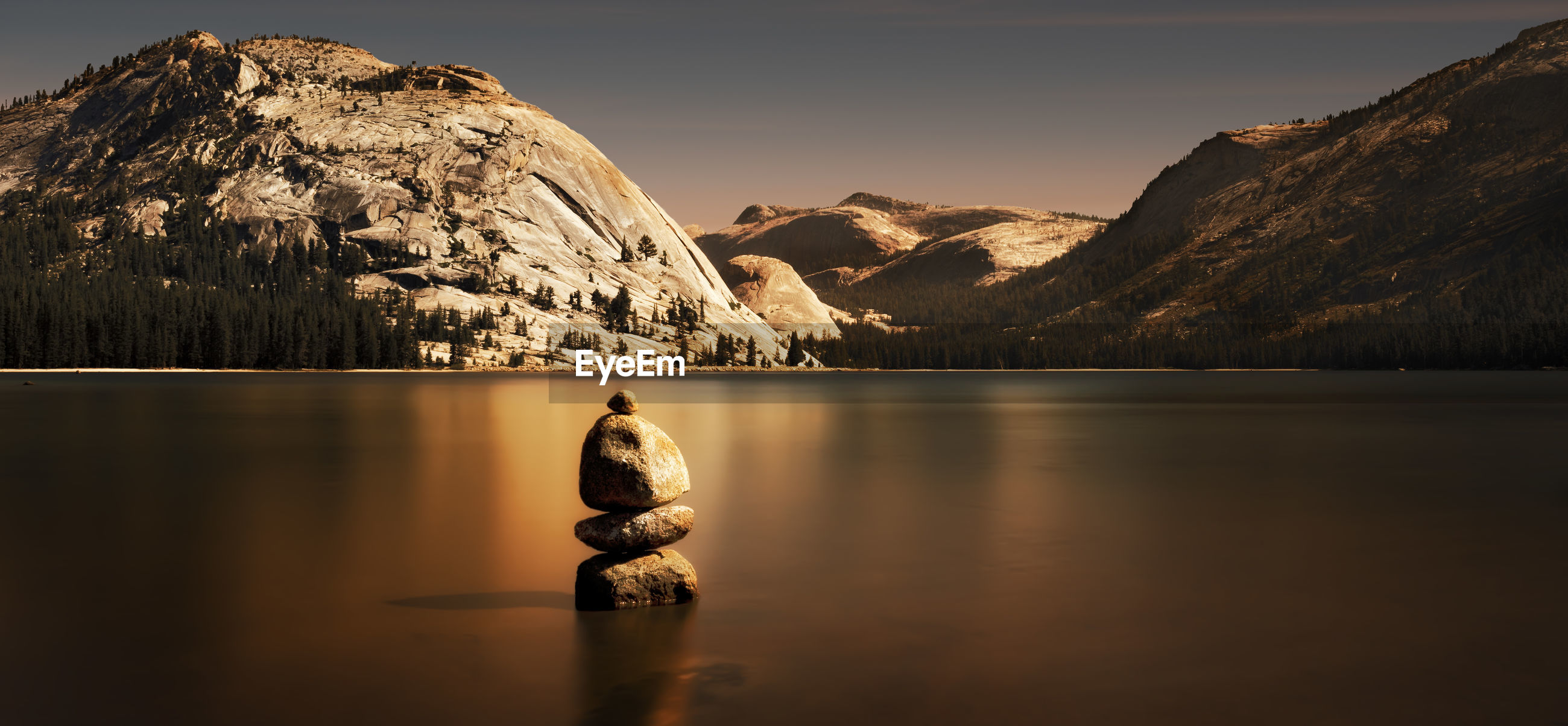 Stacked stones on calm lake against mountains at yosemite national park