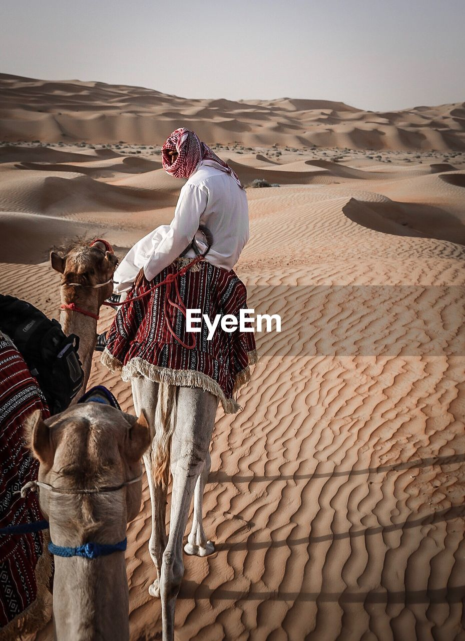 Man Riding Camel In Desert Against Clear Sky