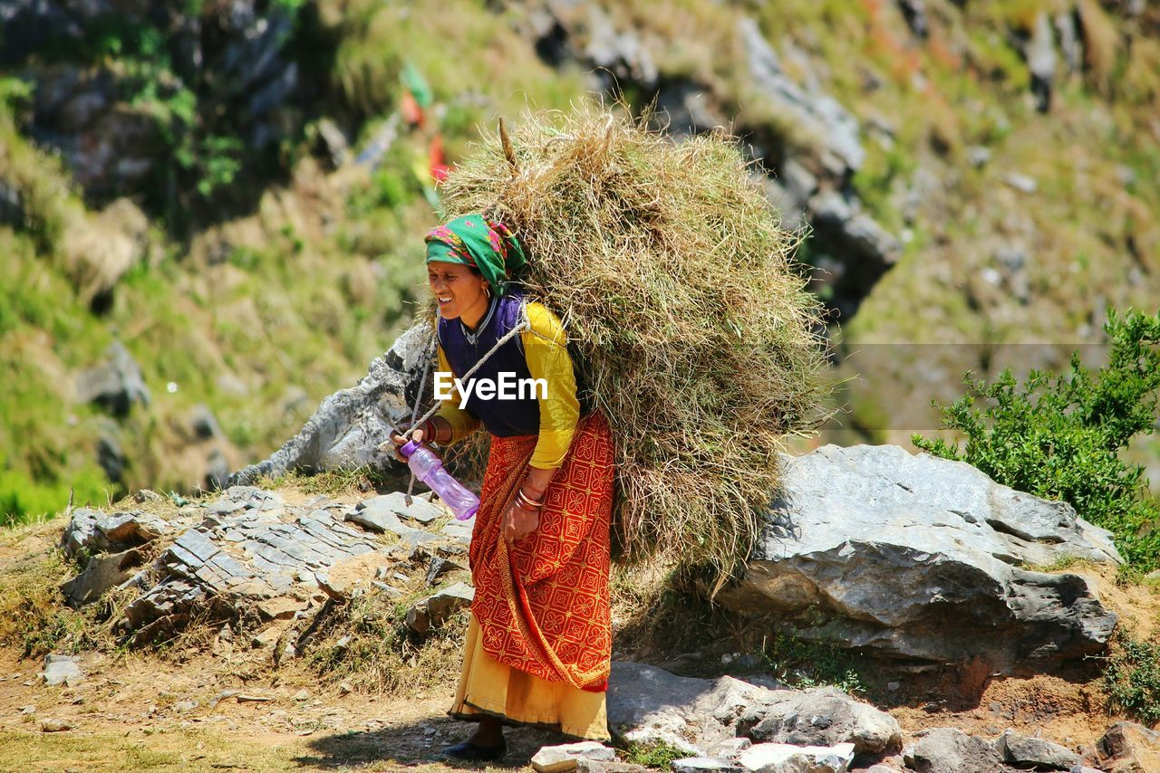 Tried Woman Carrying Grass On Shoulders And Walking In Mountain