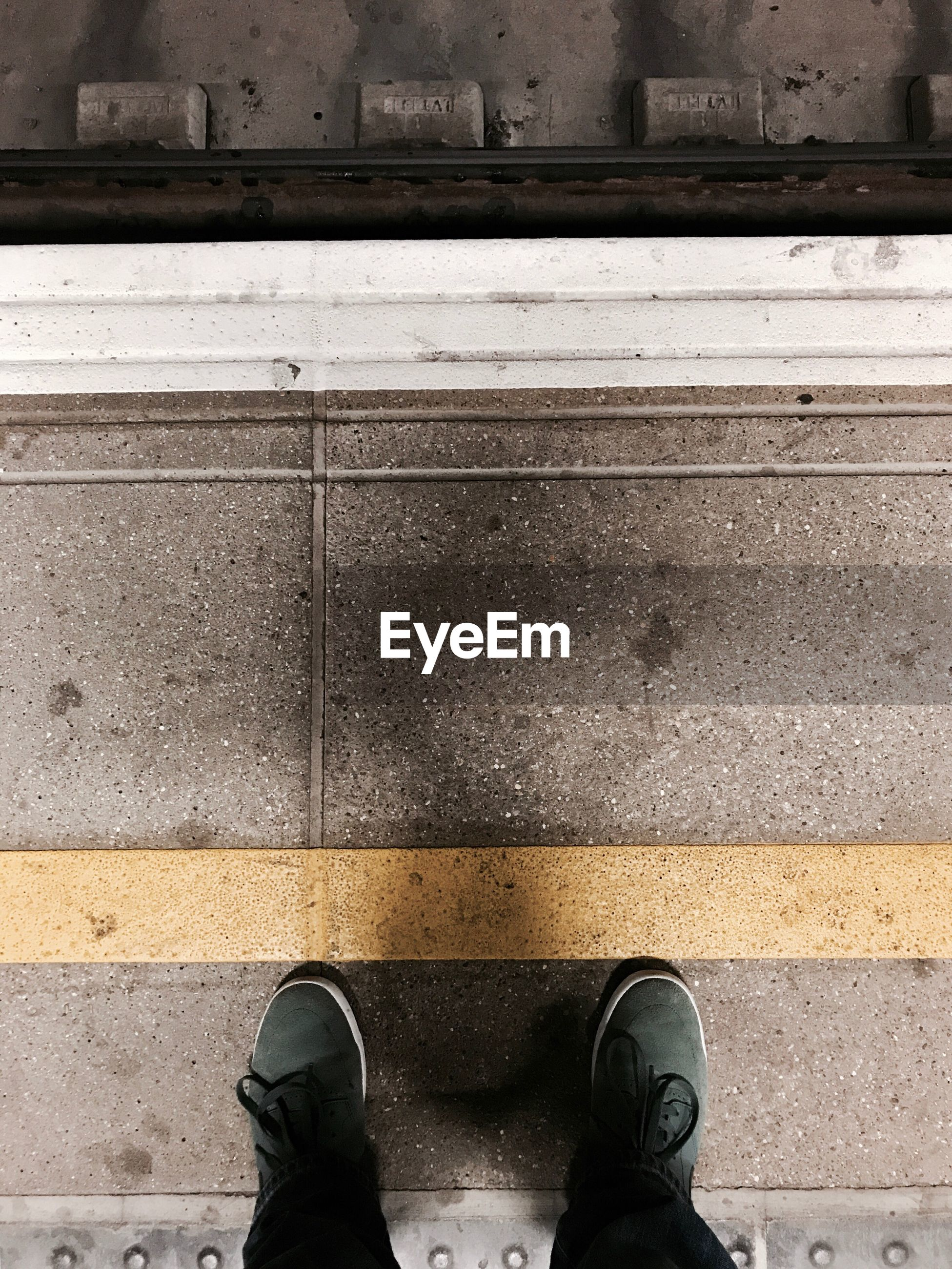 Low section of man standing at railroad station platform