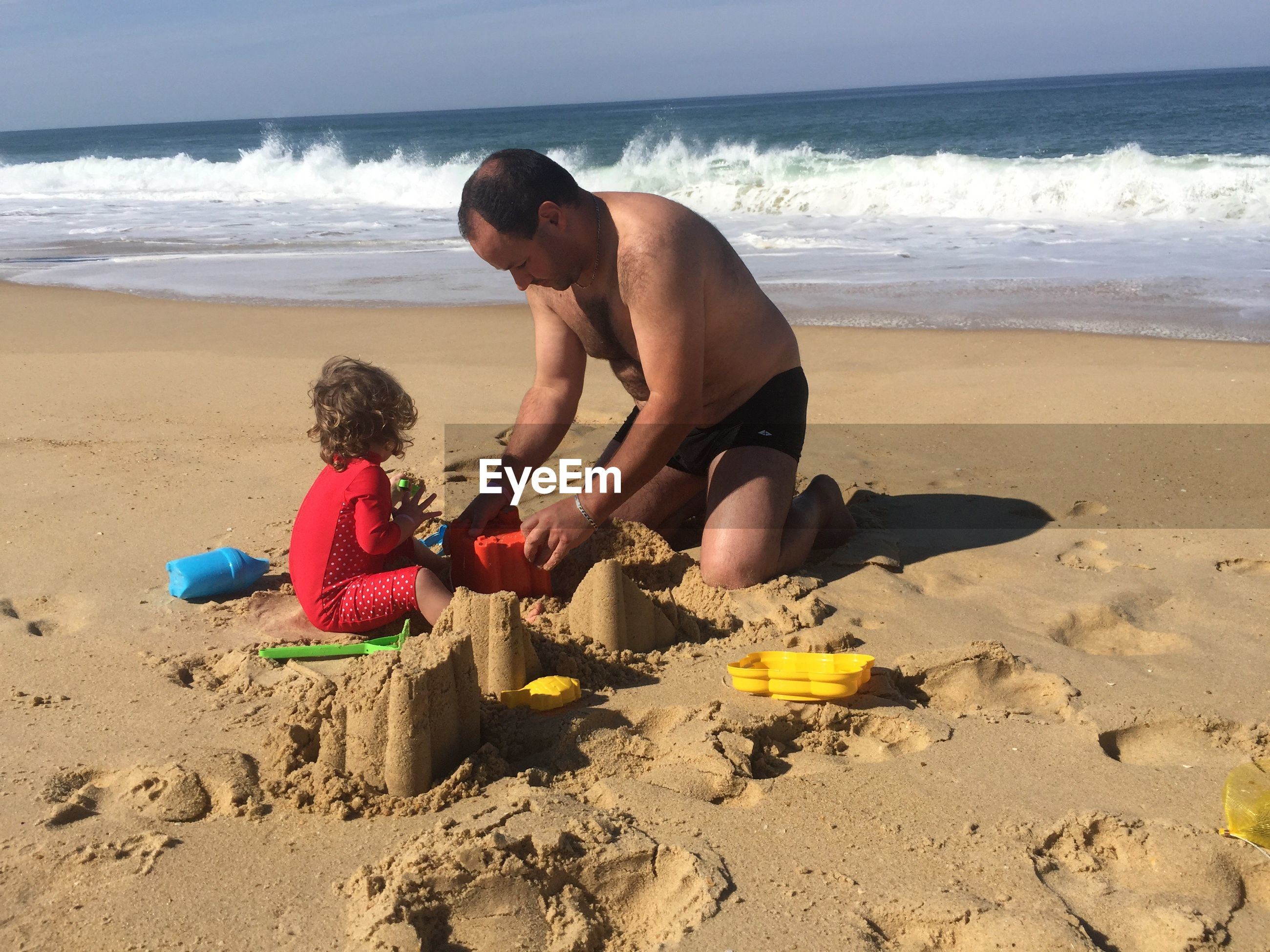 Shirtless man with son making sand castle at beach
