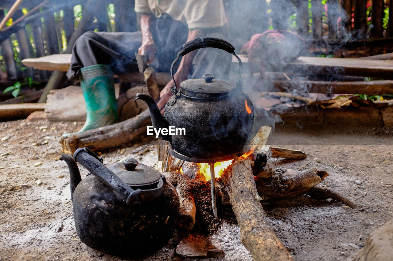 Kettle on fire with person cutting wood in background