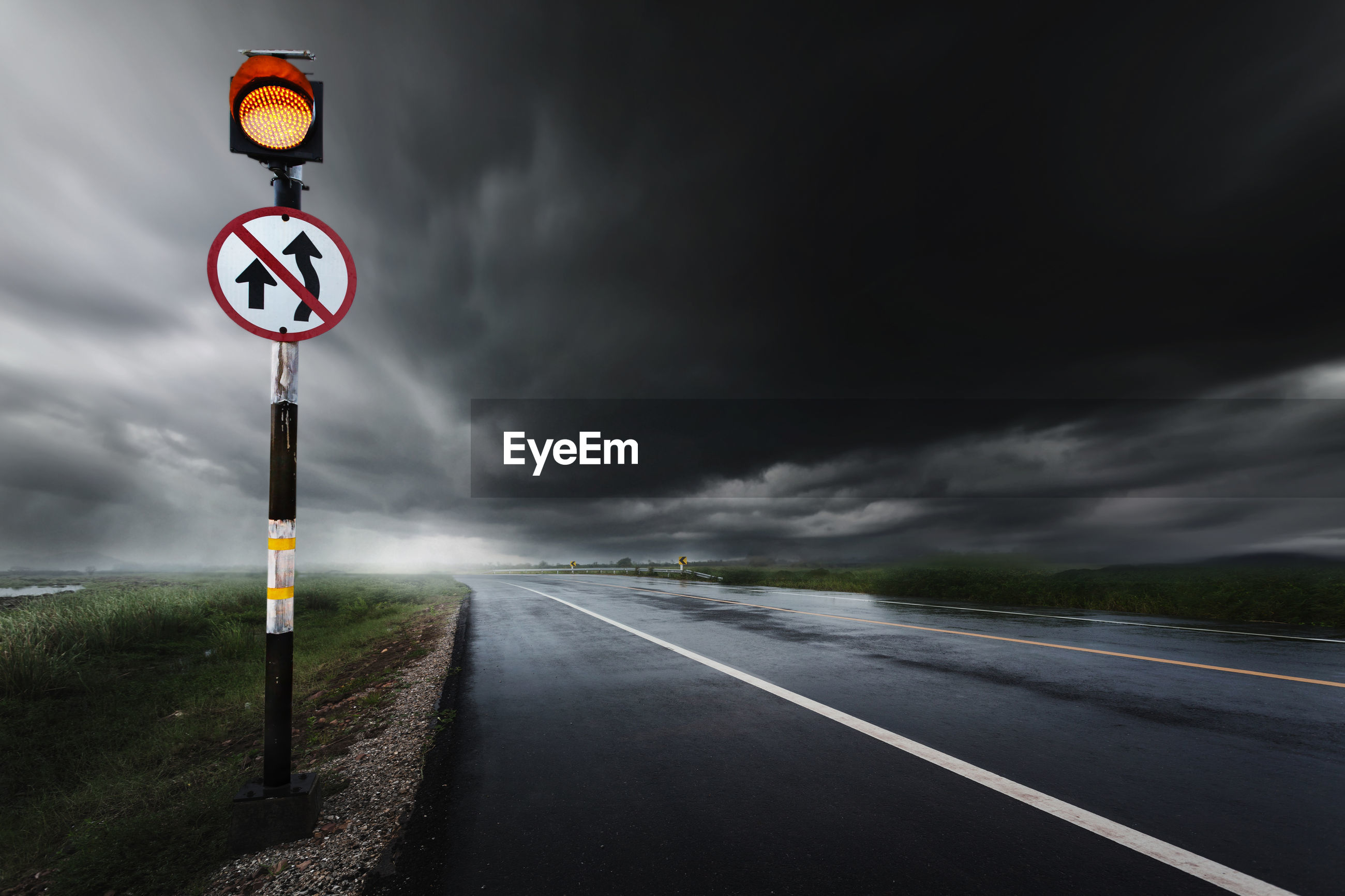 Road sign by wet road against sky