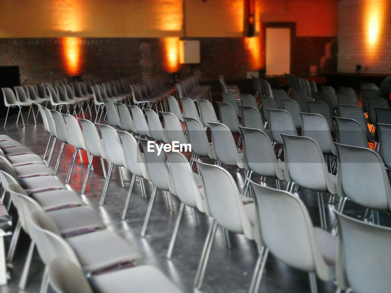 Empty chairs in illuminated seminar hall