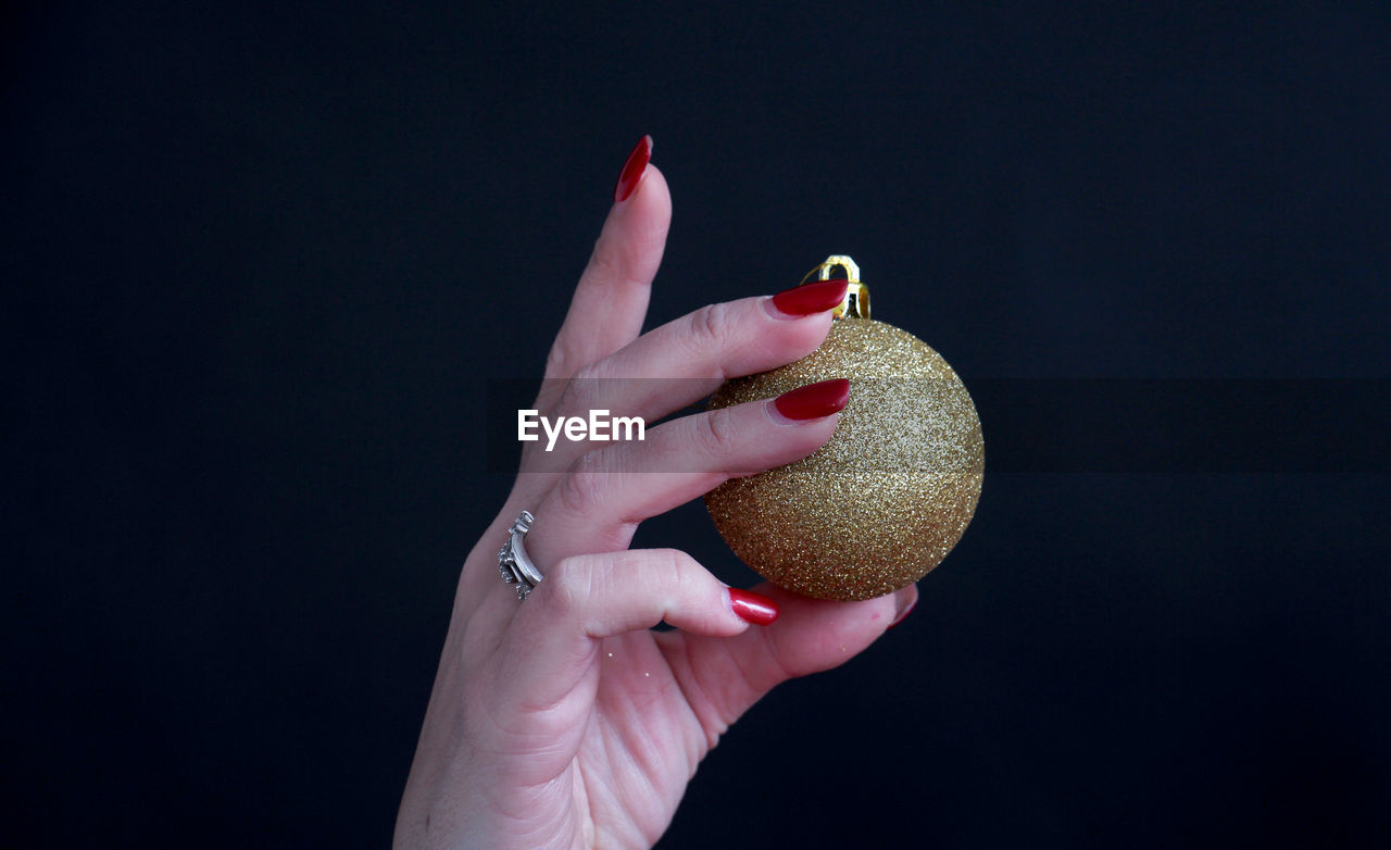 human hand, human body part, holding, black background, human finger, one person, food and drink, food, studio shot, real people, fruit, freshness, healthy eating, nail polish, women, close-up, lifestyles, fingernail, indoors, day, adult, people