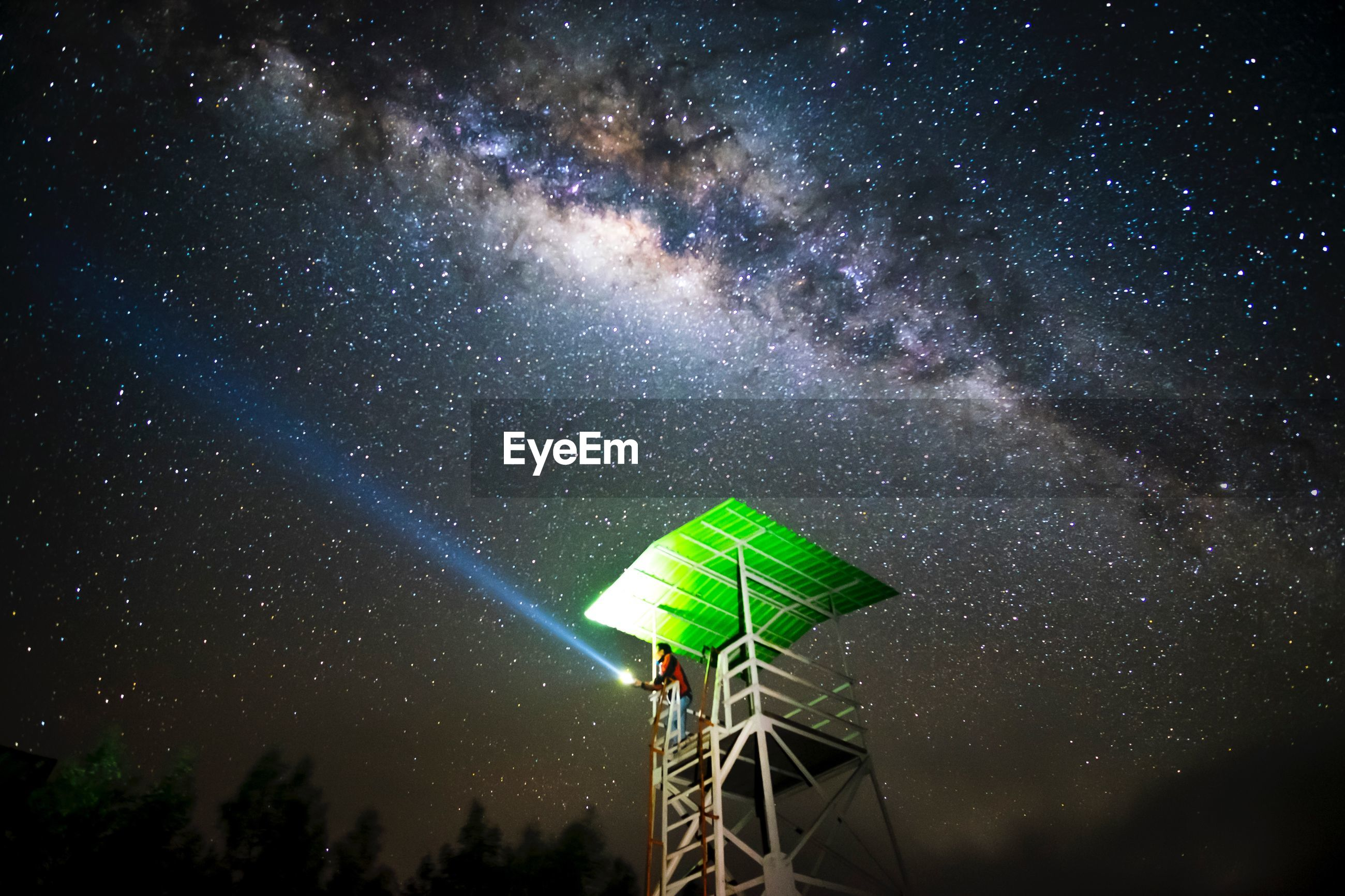 Low angle view of man holding flashlight while standing at observation point against sky during night