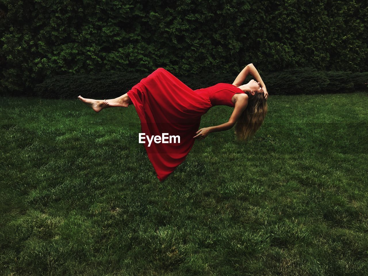 Digital Composite Image Of Woman Wearing Dress While Lying In Air Over Field