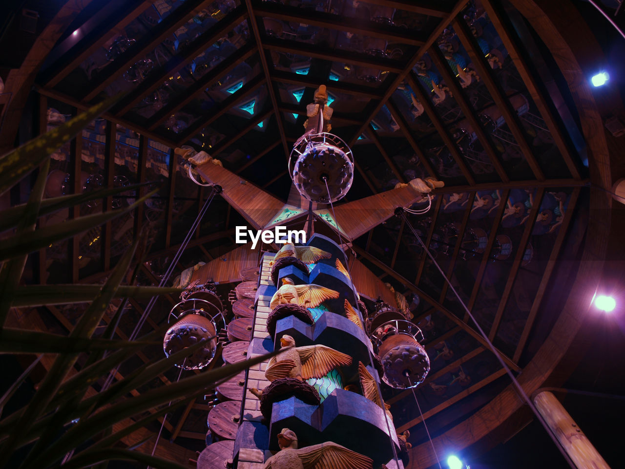 low angle view, ceiling, indoors, built structure, architecture, place of worship, spirituality, real people, hanging, statue, illuminated, day