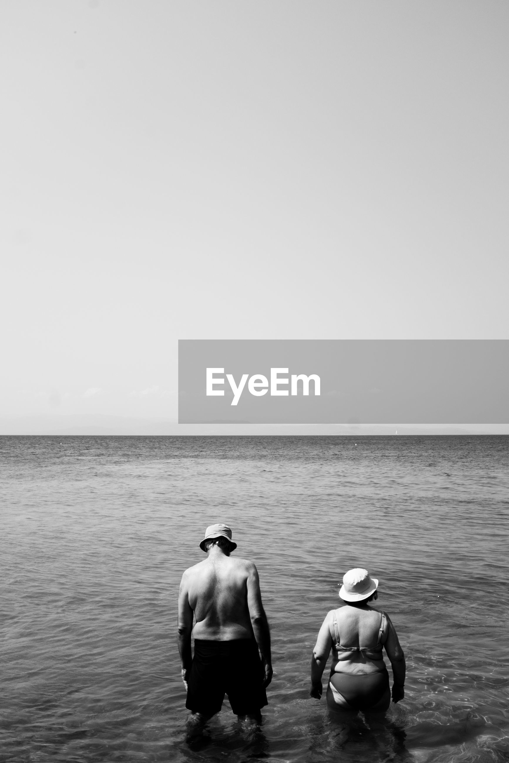 REAR VIEW OF TWO MEN IN SEA AGAINST SKY