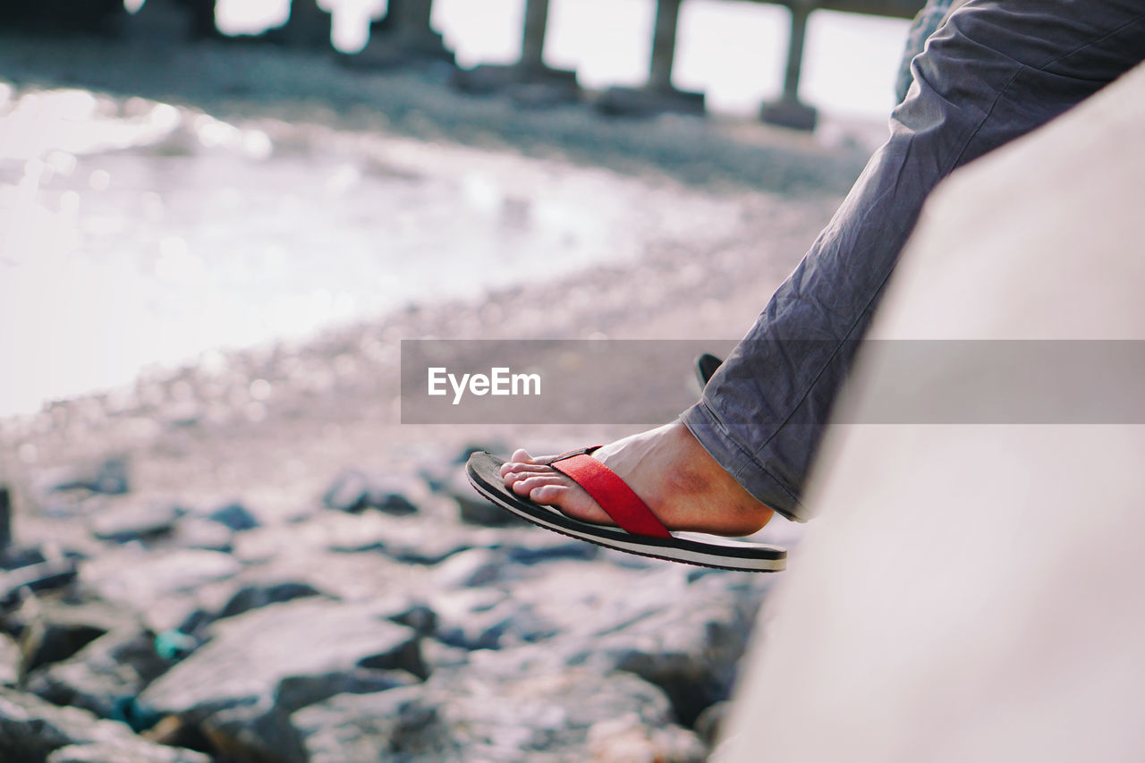 Low Section Of Person With Slipper Sitting By Sea