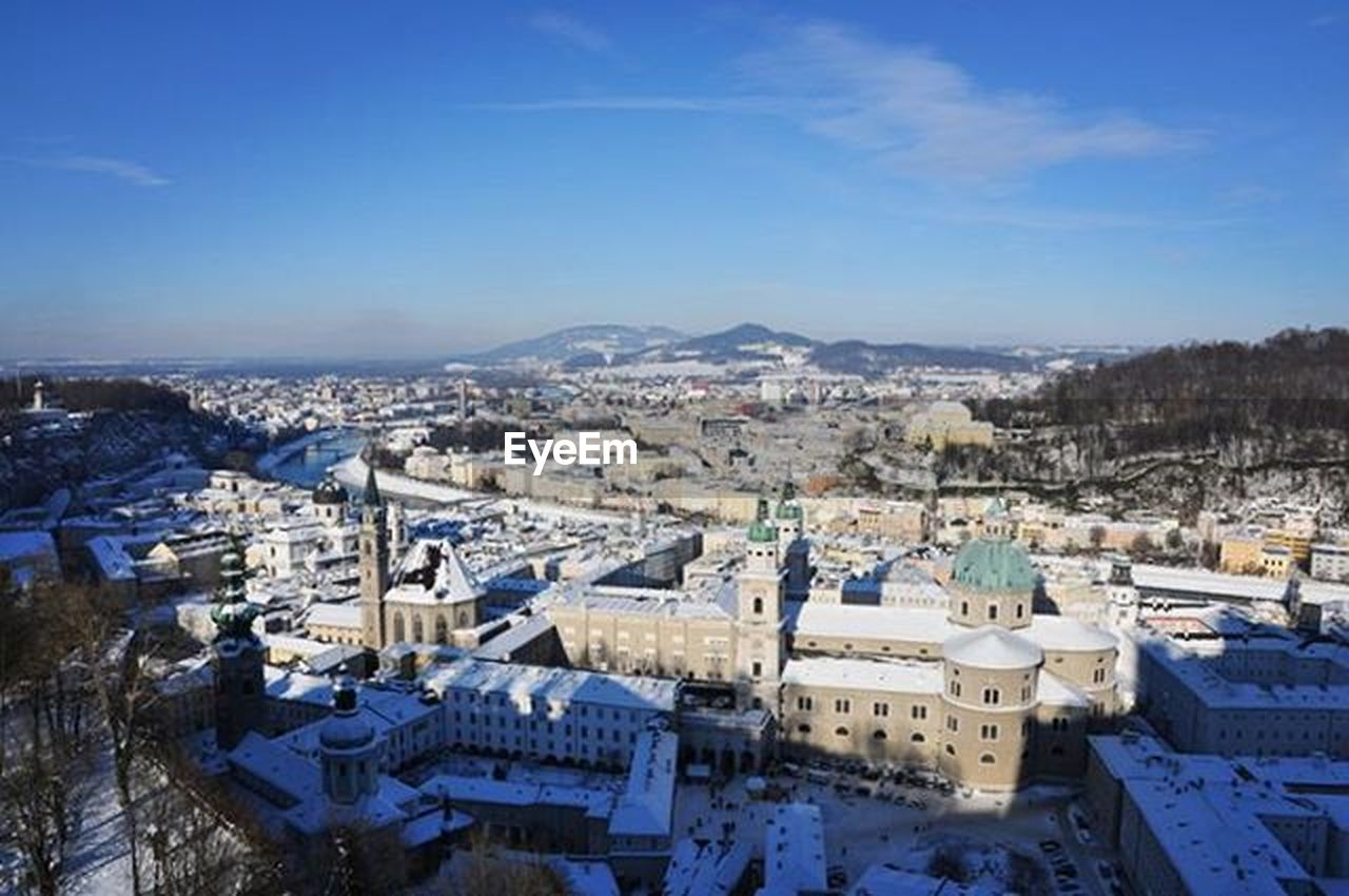 architecture, cityscape, high angle view, building exterior, snow, winter, outdoors, built structure, city, cold temperature, no people, blue, aerial view, sky, travel destinations, day, mountain