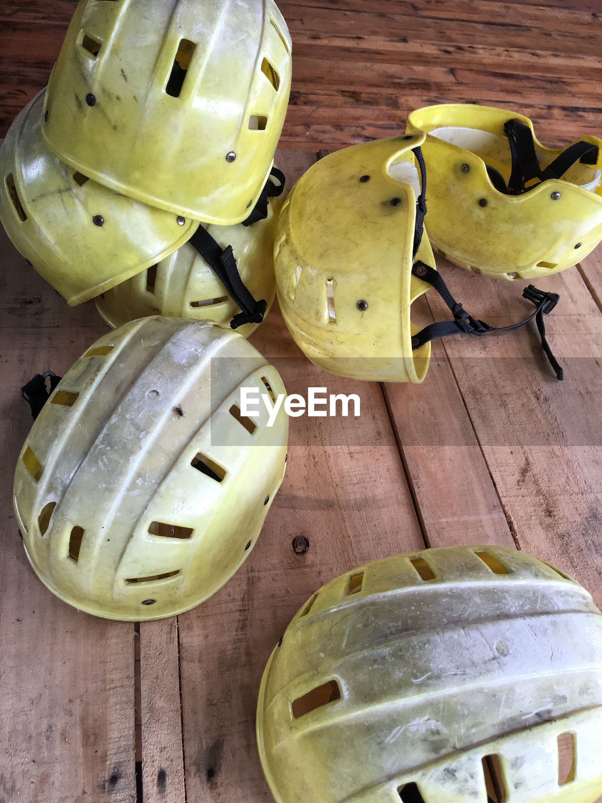 High angle view of yellow helmets on wooden floor