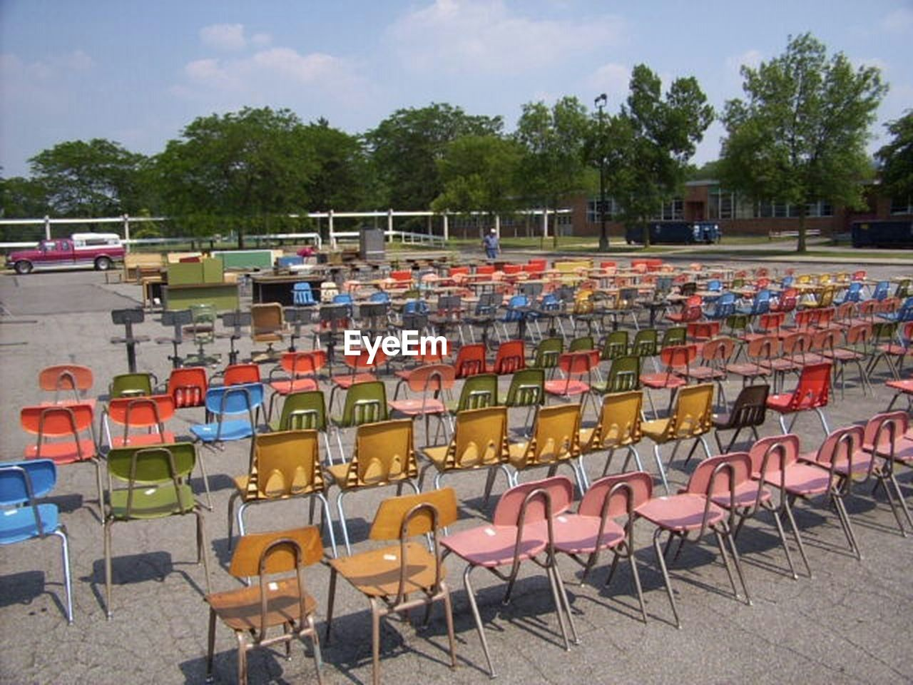 chair, in a row, seat, table, large group of objects, outdoors, day, stadium, tree, no people, competition