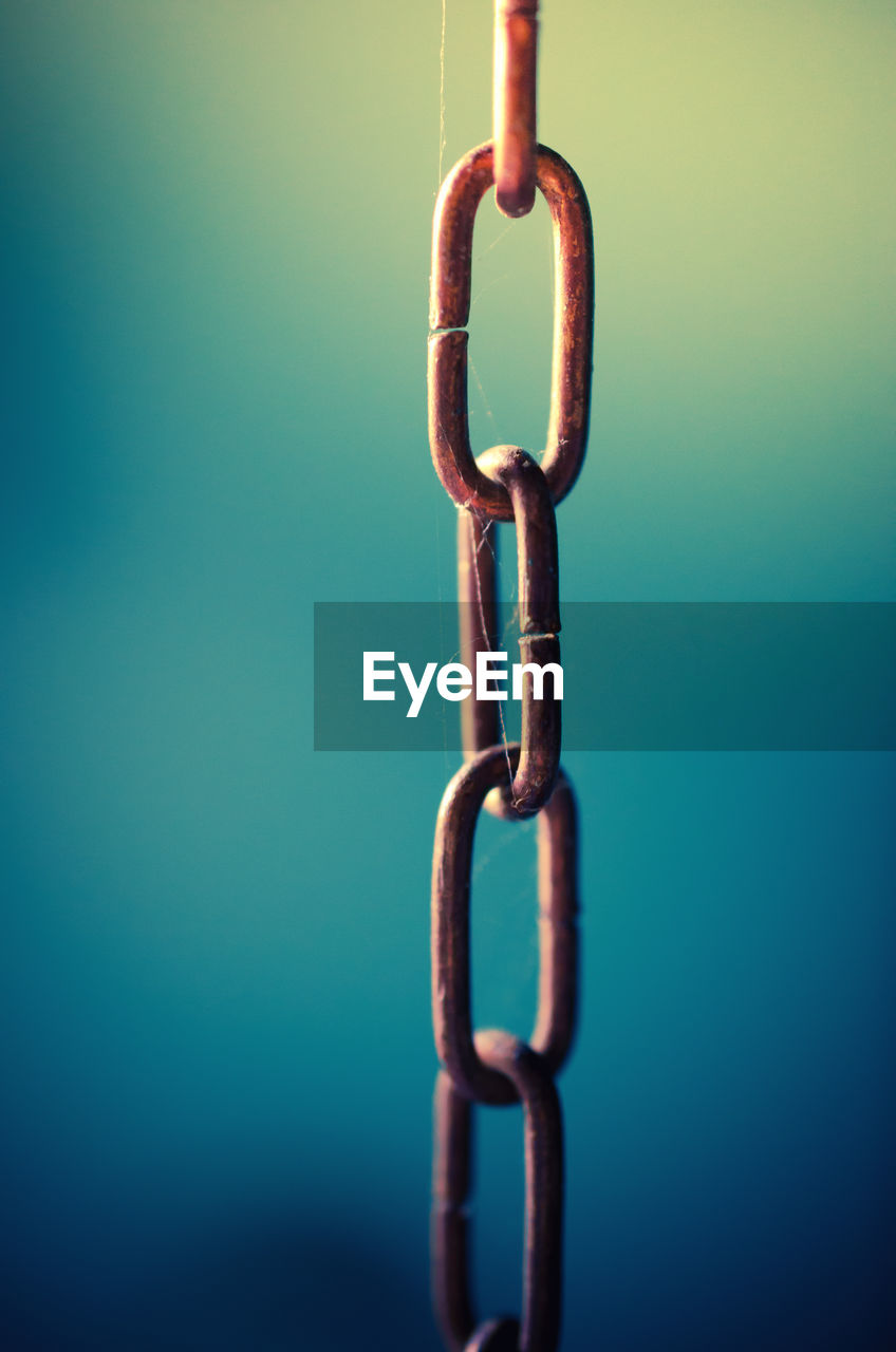 Close-up of chain against blue background