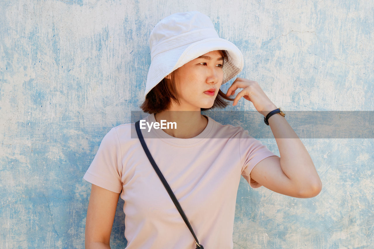 Beautiful woman wearing hat looking away while standing against wall