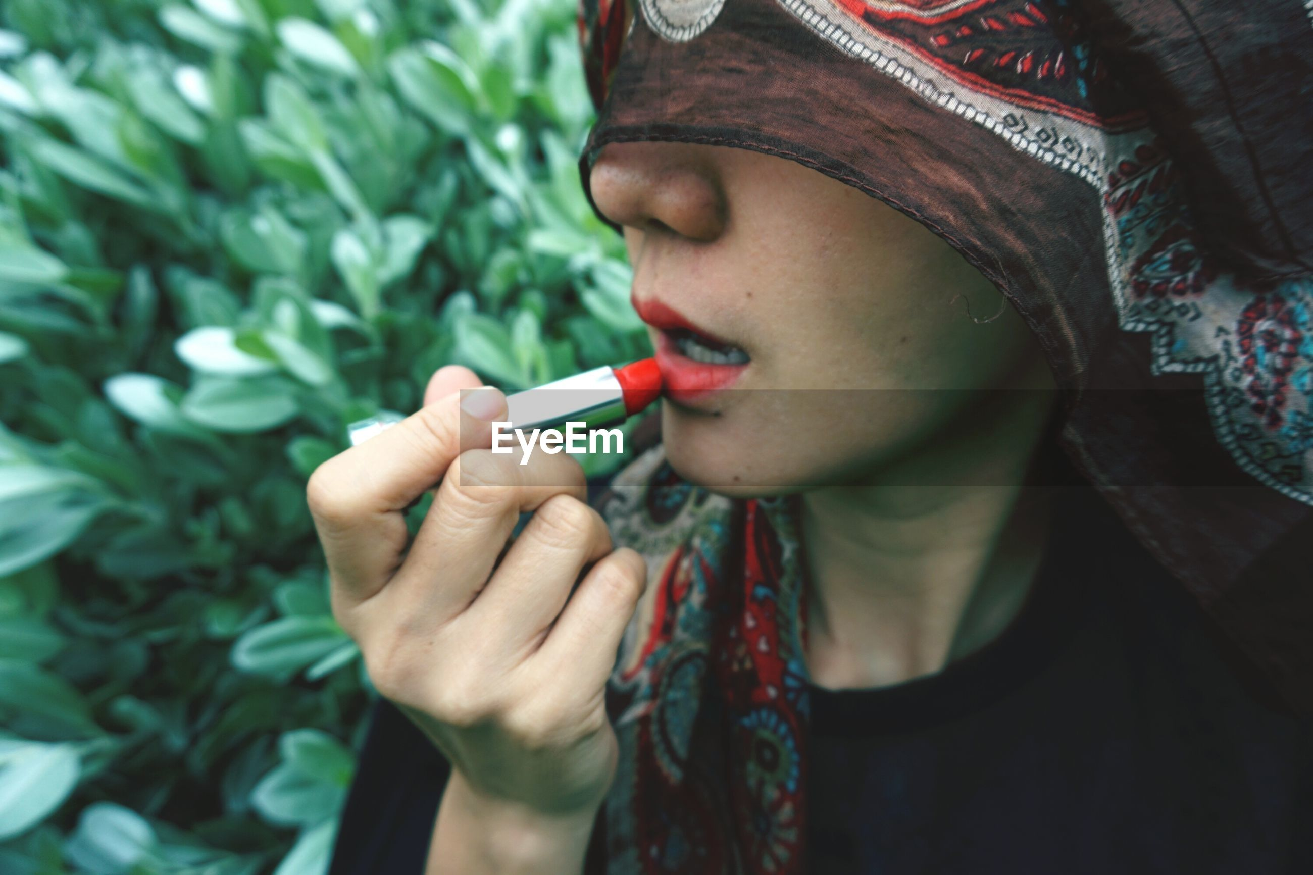 Close-up of woman applying red lipstick against plants