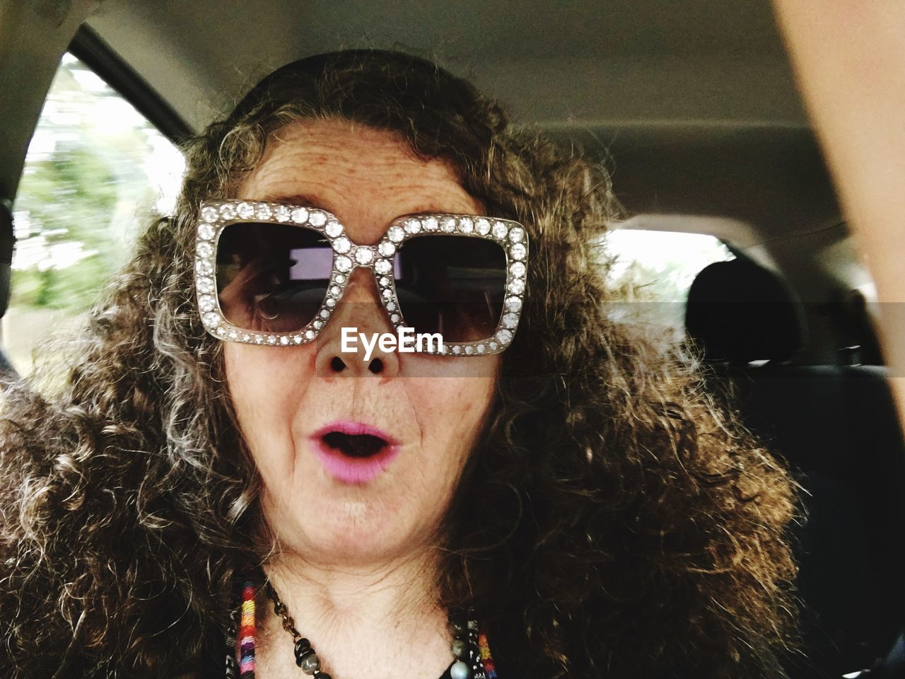 Portrait of woman wearing novelty glasses while sitting in car