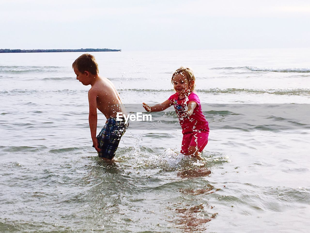 Children Playing At Sea Against Sky