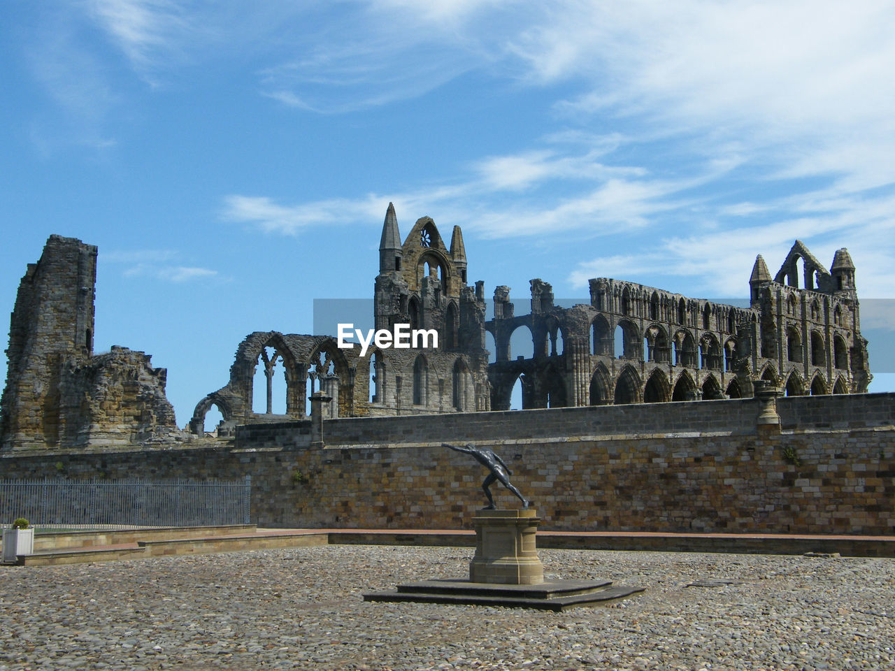 Statue At Whitby Abbey Against Cloudy Sky