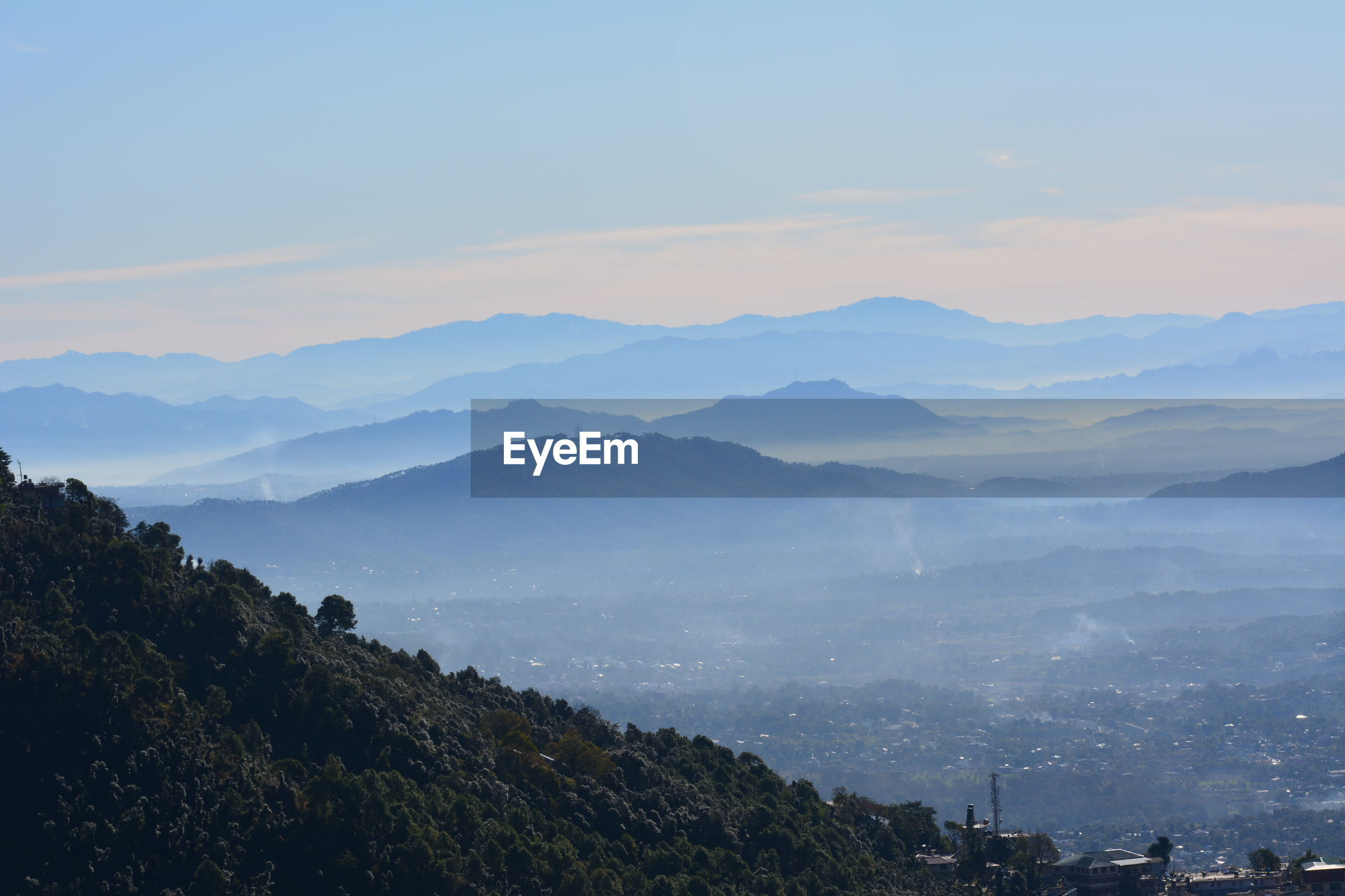 SCENIC VIEW OF MOUNTAINS AGAINST SKY IN CITY