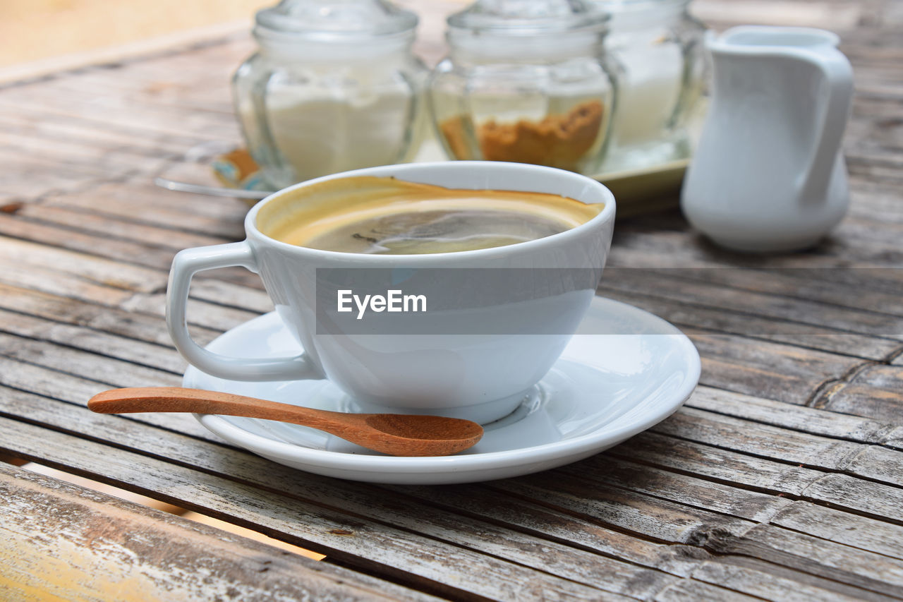 Close-Up Of Coffee Cup By Wooden Spoon On Saucer At Wooden Table