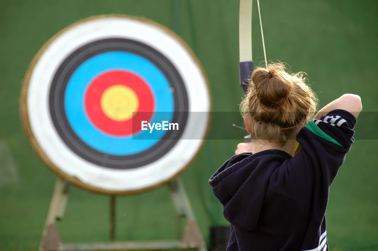 Rear view of girl aiming at target with bow and arrow
