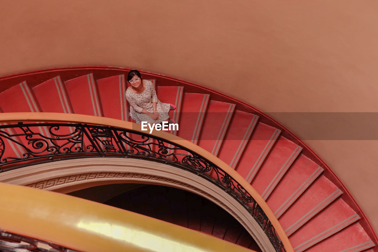 LOW ANGLE VIEW OF SPIRAL STAIRCASE AGAINST ORANGE SKY