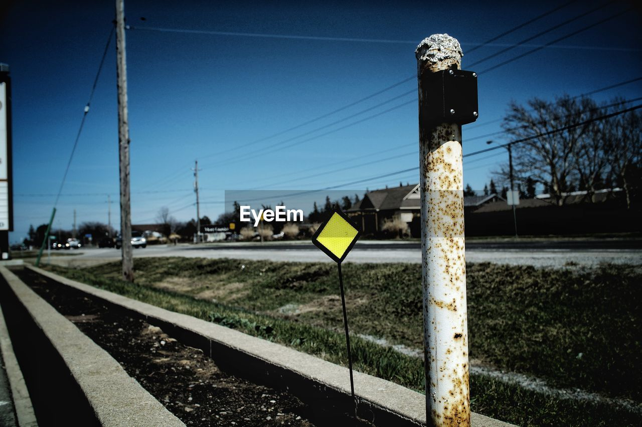 sky, transportation, sign, nature, rail transportation, day, no people, road, railroad track, track, clear sky, communication, focus on foreground, tree, pole, plant, outdoors, cable, sunlight, road sign, electricity, crossing sign