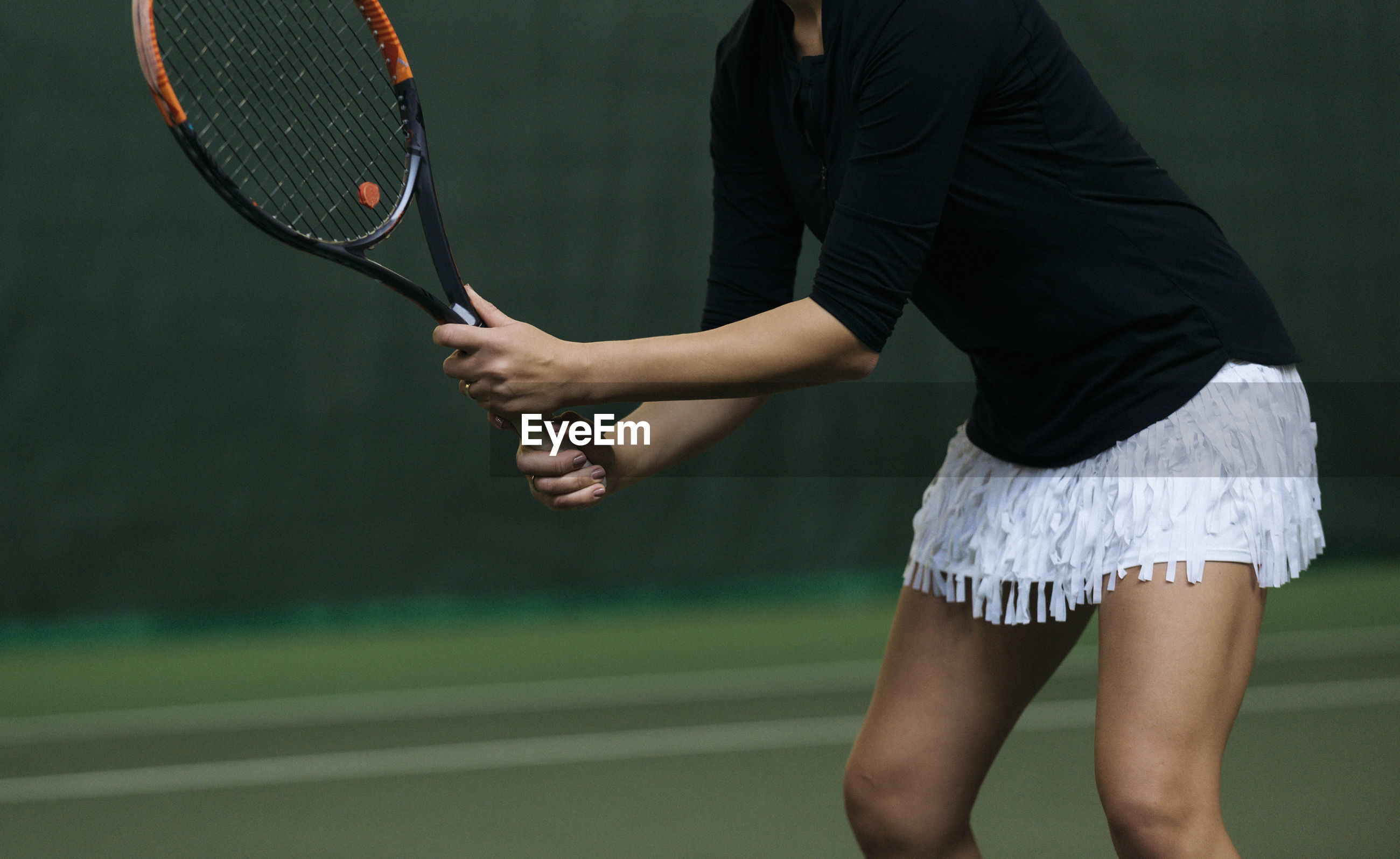 Midsection of woman playing tennis