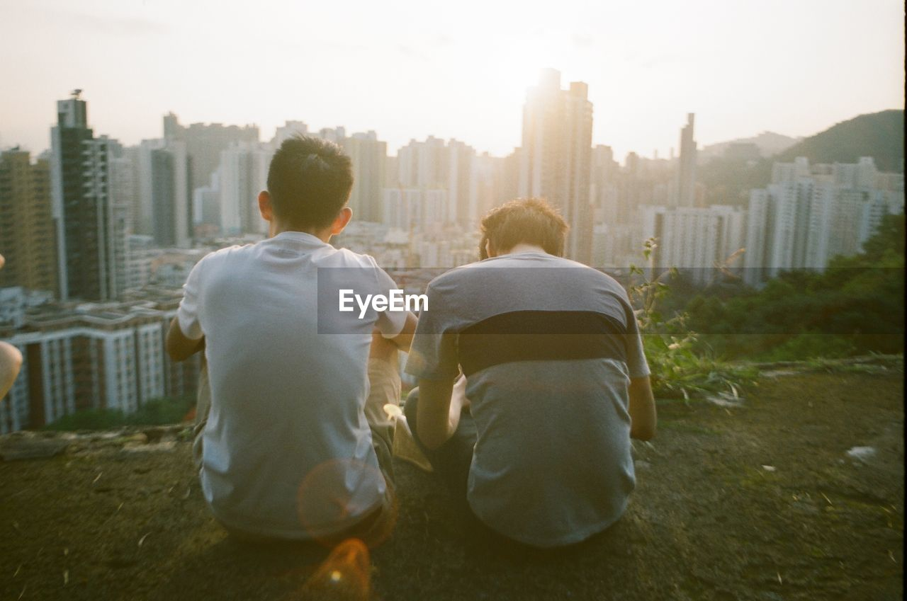 Rear View Of Friends Sitting By Cityscape Against Sky At Morning