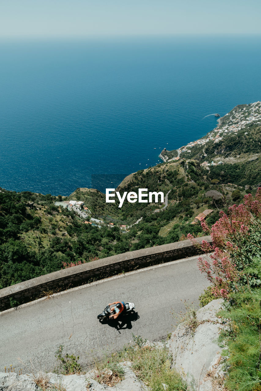 sea, nature, day, high angle view, road, transportation, water, scenics, outdoors, beauty in nature, real people, motorcycle, men, sitting, tree, one person, mountain, horizon over water, mammal, sky, people