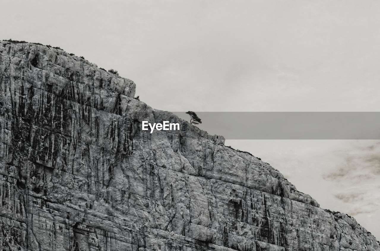 LOW ANGLE VIEW OF A ROCKY MOUNTAIN