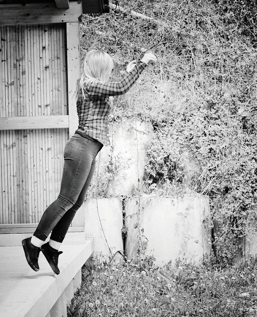 Side view full length of woman jumping from porch