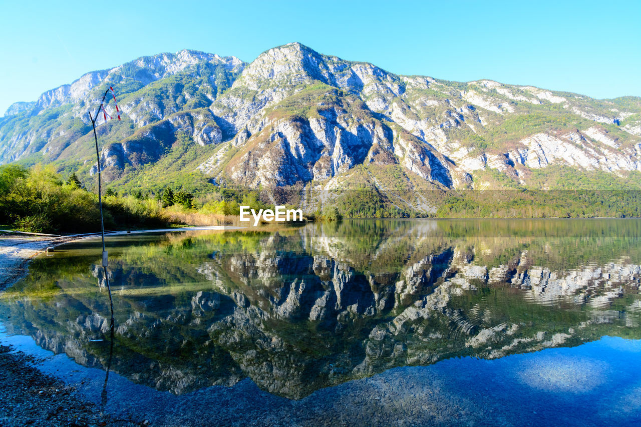 water, reflection, scenics - nature, lake, beauty in nature, tranquil scene, mountain, sky, tranquility, nature, no people, day, blue, idyllic, environment, non-urban scene, clear sky, waterfront, mountain range, outdoors