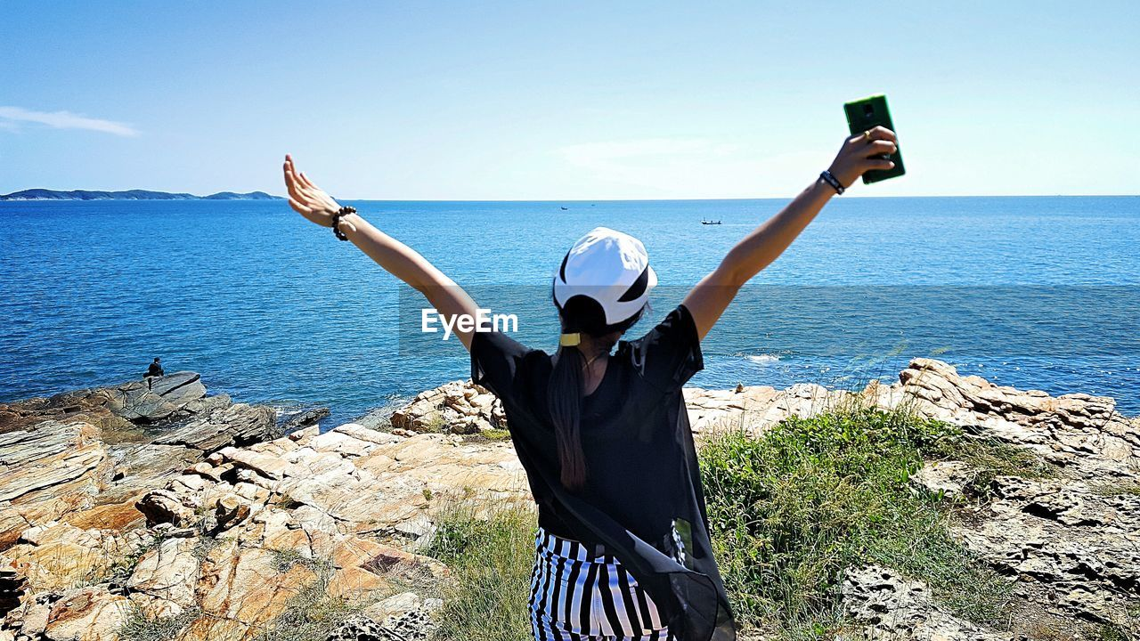 Woman with arms raised looking at sea while standing on cliff