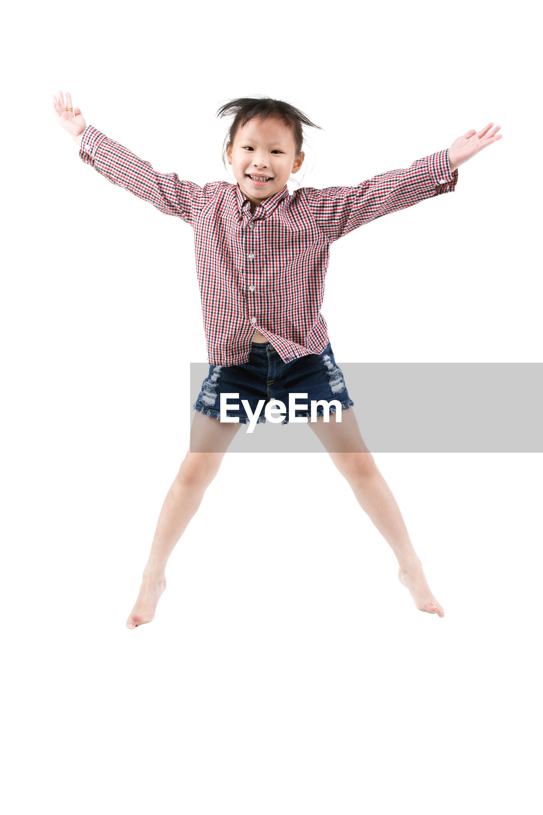 Portrait of cute happy girl jumping against white background