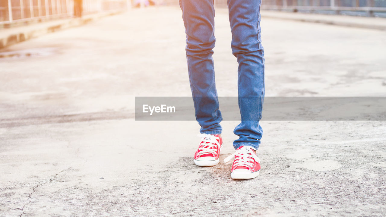 low section, one person, human leg, body part, human body part, standing, shoe, real people, day, lifestyles, city, outdoors, canvas shoe, jeans, casual clothing, focus on foreground, leisure activity, footpath, street, human foot, human limb