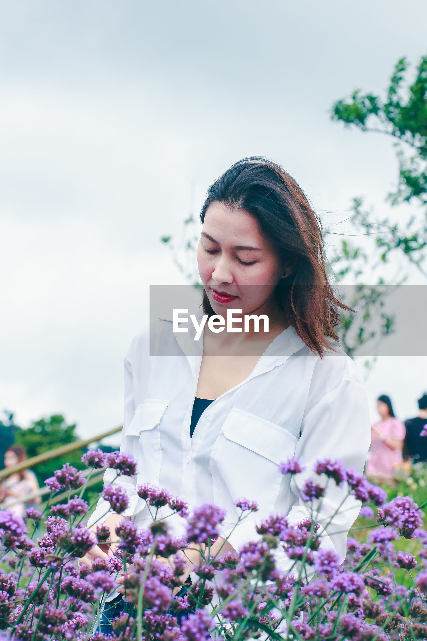 BEAUTIFUL YOUNG WOMAN WITH PURPLE FLOWER AGAINST SKY
