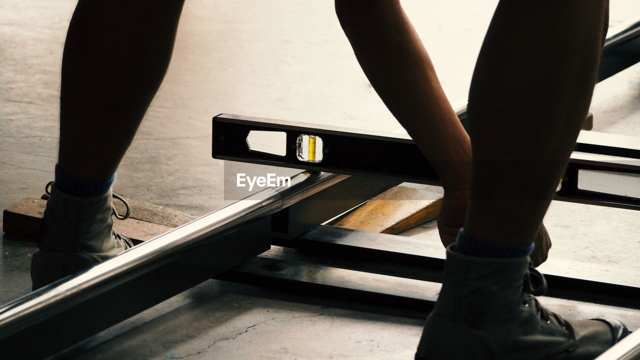 Low Section Of Worker Using Spirit Level While Measuring Metal