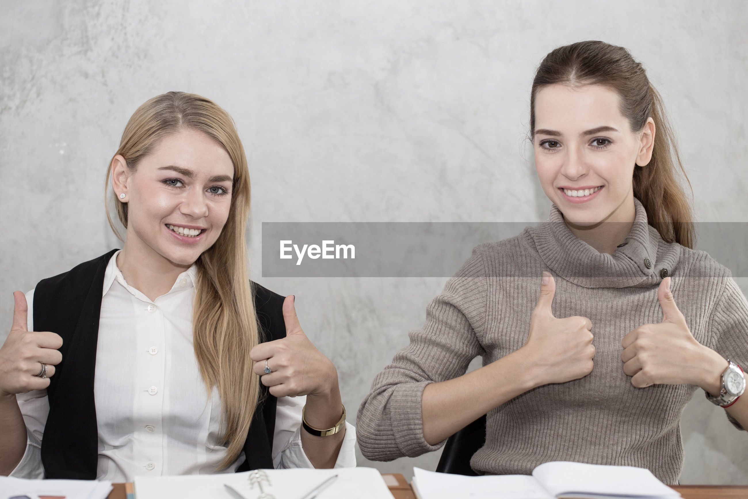 Portrait of confident businesswomen showing thumbs up while sitting at desk in office