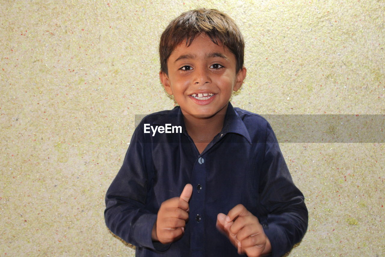 PORTRAIT OF A SMILING BOY HOLDING A CAMERA