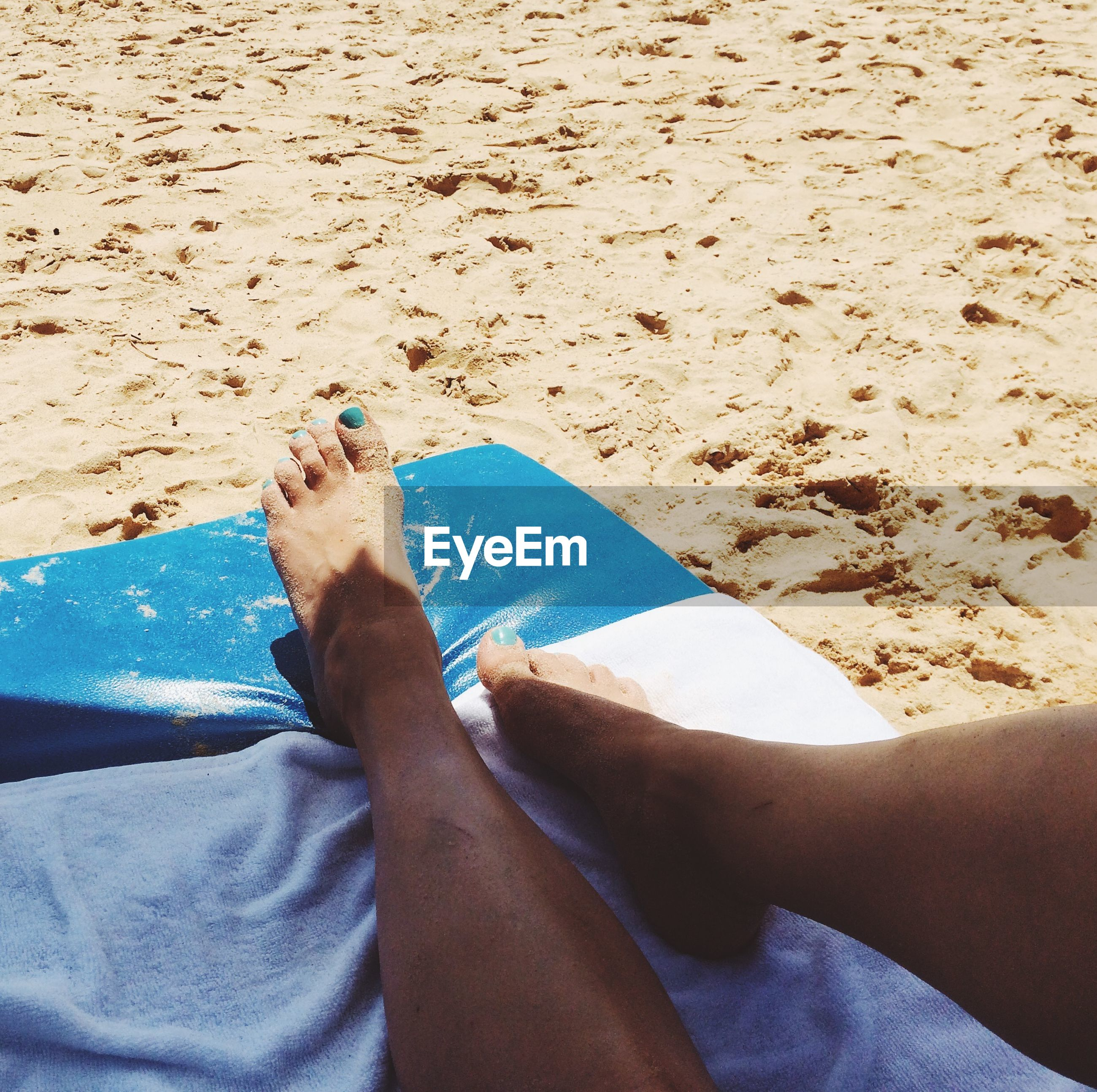 Low section of woman lying at beach