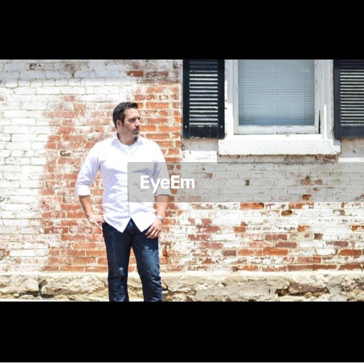 one man only, only men, brick wall, mid adult, standing, one person, adult, mid adult men, adults only, casual clothing, front view, men, one mature man only, mature adult, people, building exterior, portrait, architecture, day, full length, outdoors, city, young adult
