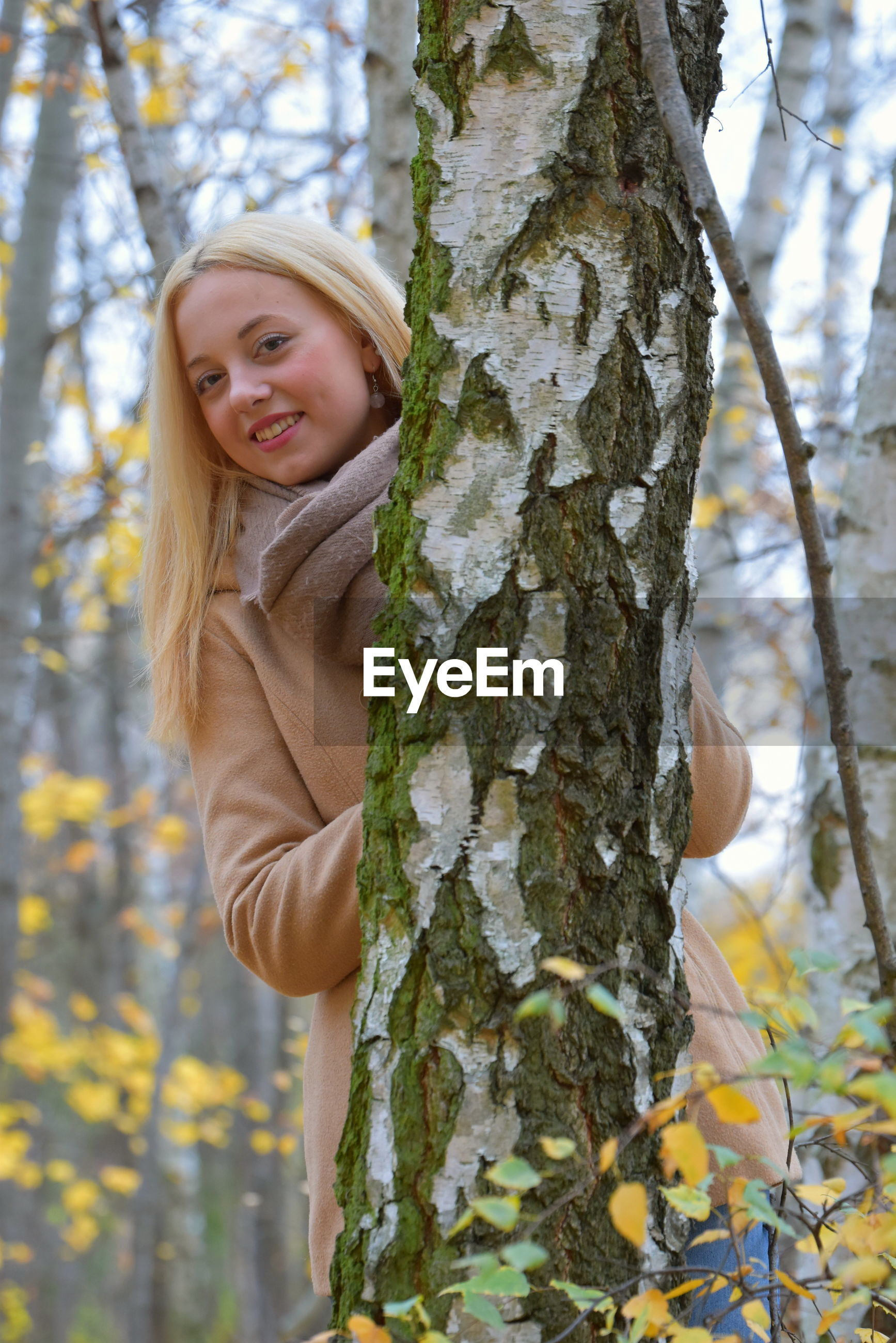 Portrait of smiling young woman at forest during autumn